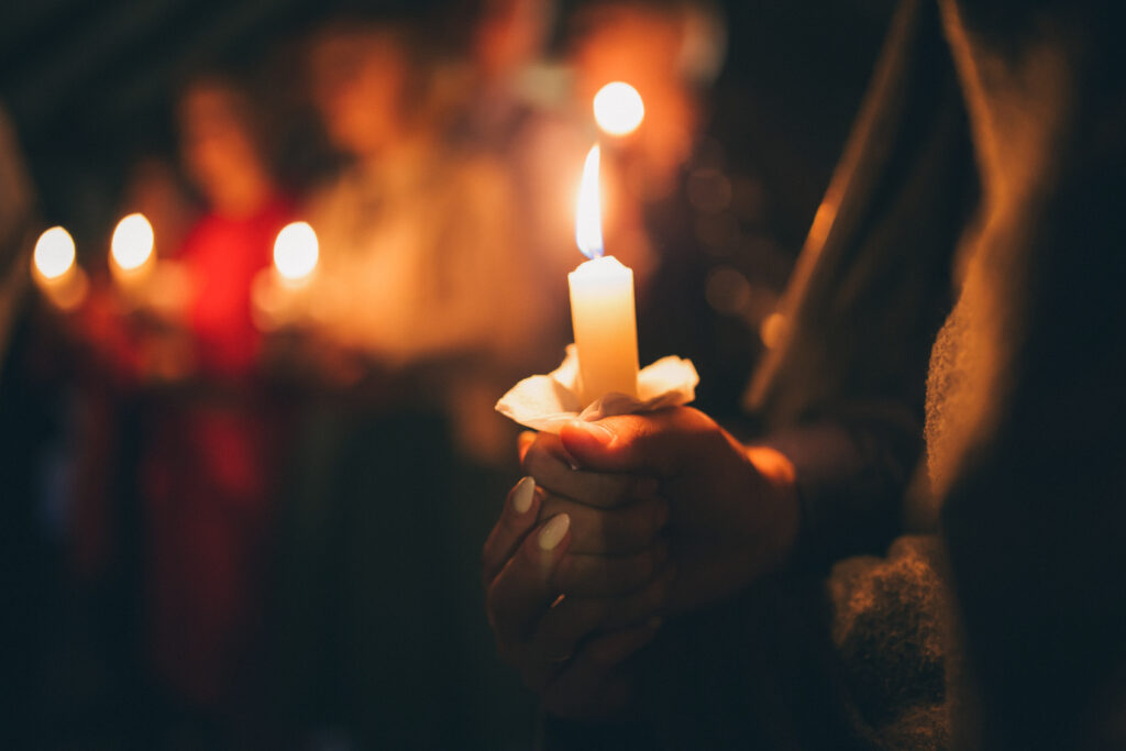 A,Girl,Holds,A,Lighted,Candle,In,Her,Hands,,A